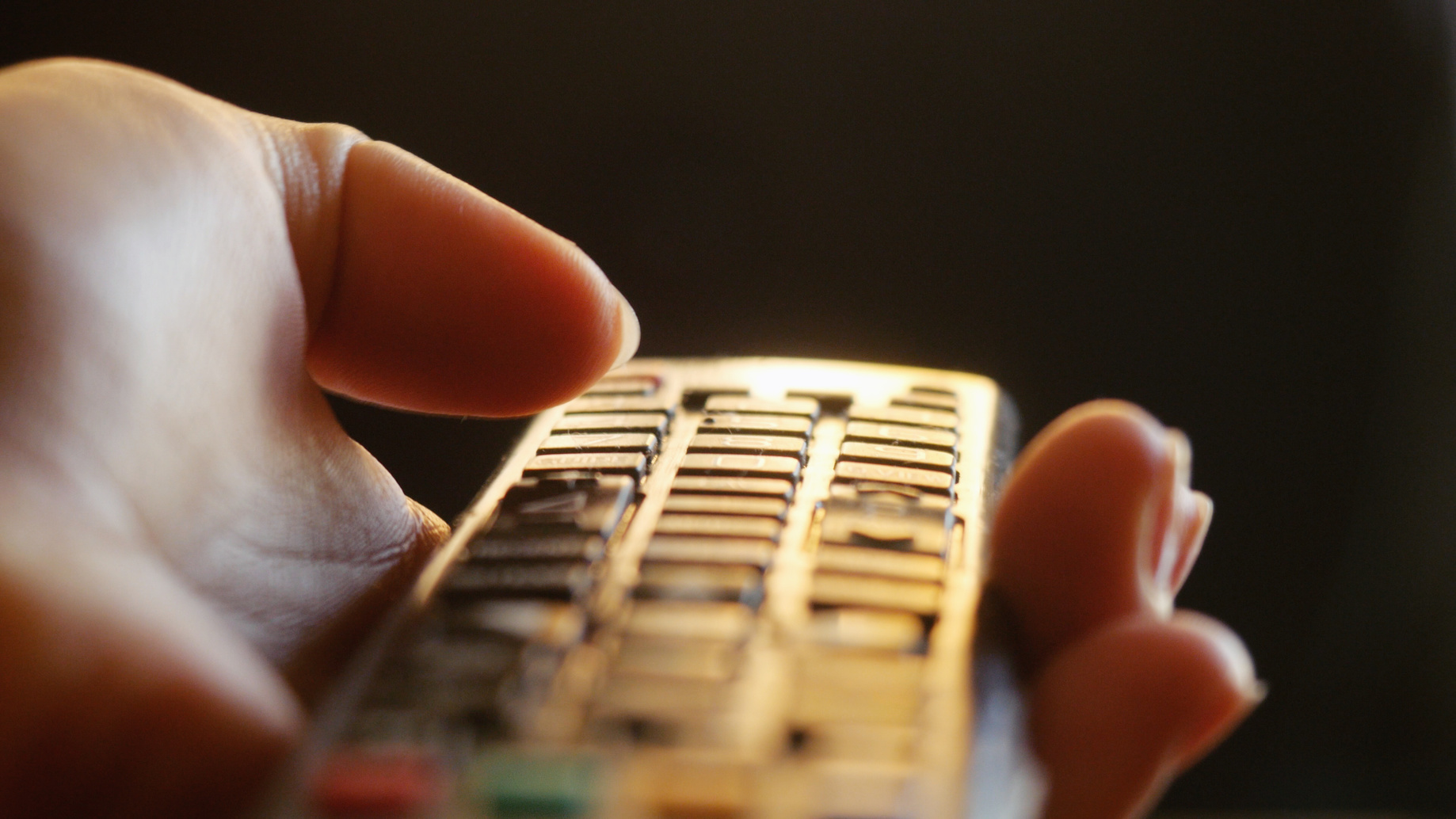 Close up of woman's hand with a television remote control changing channels at sunset time