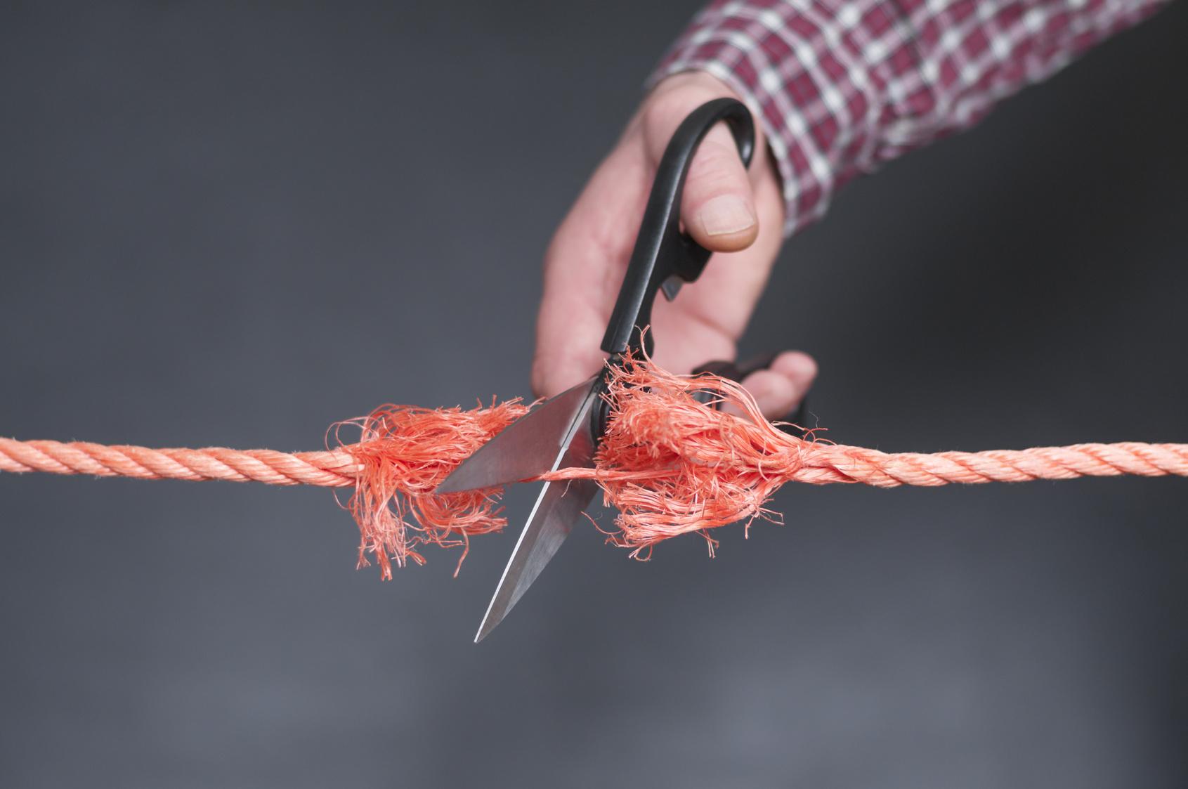 Rotes Seil wird zerschnitten / Rotes Seil wird mit einer Schere zerschnitten.